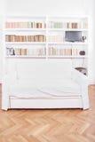 有沙发或长沙发的家庭书库在白色客厅 免版税库存照片