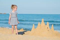 有沙子城堡的小女孩 库存照片