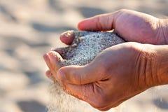 有沙子的手 免版税图库摄影