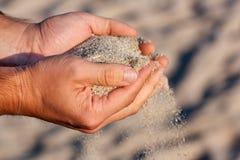 有沙子的手 免版税库存照片