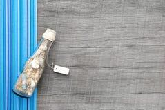 有沙子的纪念品在木背景的瓶和贝壳 库存照片
