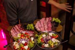 有沙拉叶子和夏天沙拉的两肉板材在侍者` s手上 免版税库存照片