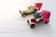 有沙滩伞的两辆小玩具汽车 旅行的概念 免版税图库摄影
