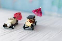 有沙滩伞的两辆小玩具汽车 旅行的概念 免版税库存图片