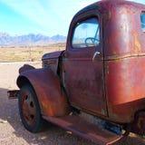 有沙漠大农场和山的老生锈的卡车 免版税库存照片