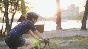 有河、城市和日落的年轻女性乘坐的自行车在背景 r 股票录像