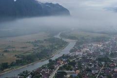 有河的在薄雾的村庄和山 库存照片