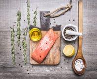有油、柠檬、盐和胡椒的,在一个切板的草本三文鱼内圆角在木土气背景顶视图关闭 免版税库存图片