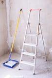 有油漆、刷子路辗油漆盘子和梯子的蓝色桶 库存图片