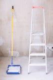 有油漆、刷子路辗油漆盘子和梯子的蓝色桶 免版税图库摄影
