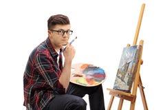 有油漆刷和调色板的少年画家 免版税图库摄影