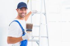 有油漆刷的愉快的杂物工,当爬梯子时 库存照片