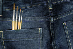 有油漆刷的蓝色牛仔裤 库存照片