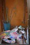 有油漆和刷子的老调色板 免版税库存照片