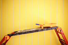 有油漆和路辗盘子的梯凳平台,对背景明亮的黄色墙壁,复制空间文本的 图库摄影