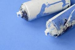 有油漆滴水的一些使用的蓝色烟雾剂喷射罐头在软和毛茸的浅兰的羊毛织品毯子说谎  经典女性de 免版税图库摄影