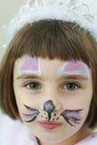 有油漆的小女孩在她的面孔 免版税库存照片