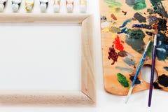 有油漆的艺术调色板和在白色背景的一把刷子 图库摄影