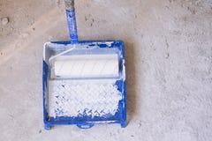 有油漆的蓝色桶和刷子路辗绘盘子 库存照片