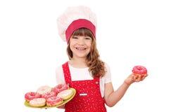 有油炸圈饼的小女孩厨师 免版税库存照片