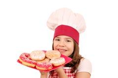 有油炸圈饼的小女孩厨师 免版税库存图片