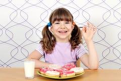 有油炸圈饼的小女孩和好手签字 免版税图库摄影