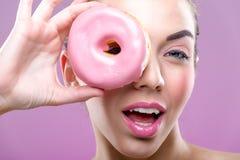 有油炸圈饼的美丽的妇女,一只眼睛比食用一个桃红色多福饼 免版税库存照片