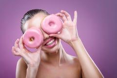 有油炸圈饼的美丽的妇女,他的两只眼睛是桃红色多福饼 库存照片