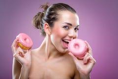 有油炸圈饼的美丽的妇女 您可以吃? 库存图片