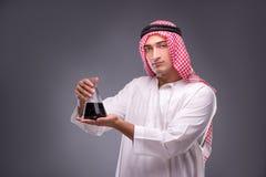 有油的阿拉伯人在灰色背景 免版税库存照片