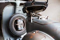 有油罐头的备用轮胎老,生锈的意大利滑行车 库存照片