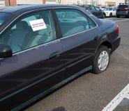 有泄了气的轮胎的老汽车在与贴纸的停车场在说放弃的窗口 图库摄影