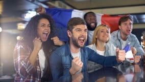 有法国旗子的愉快的足球迷庆祝在比赛,爱国者的胜利 库存图片
