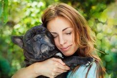 有法国牛头犬的愉快的妇女 库存图片