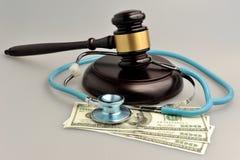 有法官惊堂木的,在灰色背景的金钱听诊器 免版税库存照片