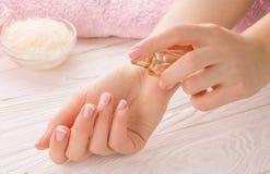 有法式修剪的妇女应用在腕子的香水 免版税库存图片