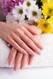 有法式修剪的美丽的手指在毛巾 免版税库存照片