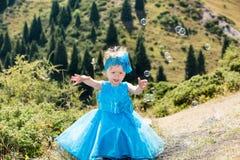 有泡影吹风机的可爱的小孩女孩在草甸的草 夏天绿色自然 库存图片