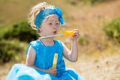 有泡影吹风机的可爱的小孩女孩在草甸的草 夏天绿色自然 免版税库存照片