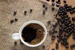 有泡影和豆的咖啡杯在大袋背景,顶视图 图库摄影
