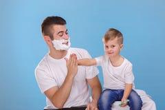 有泡沫的一个人在他的面孔握一个小男孩的手 在匙子的一个干早餐 免版税库存图片