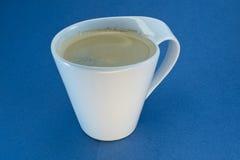 有泡沫的加奶咖啡杯在蓝色背景 免版税库存图片