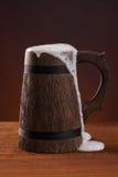 有泡沫的木啤酒杯在一个深红背景 免版税库存图片