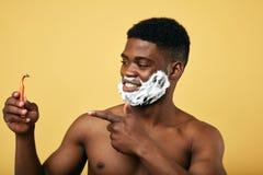 有泡沫的满意的帅哥在他的拿着剃具和指向它的面孔 免版税库存图片