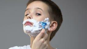 有泡沫的男孩在刮在镜子前面的面孔,模仿父亲习性 影视素材
