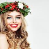 有波浪发和圣诞节花圈的美丽的微笑的妇女 免版税库存图片