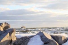 有波浪和石头的海在前景 免版税库存图片