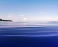 有波纹和遥远的岸的明亮的蓝色海 与海水和天空的双重风景 免版税库存照片