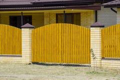 有波纹状的金属外形屋顶和木篱芭的砖房子 门面的美丽的景色 设计样式  图库摄影