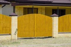 有波纹状的金属外形屋顶和木篱芭的砖房子 免版税库存图片